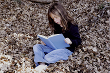 Picture of girl sitting in leaves reading a book